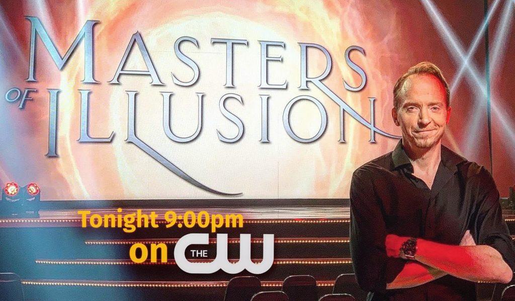 Håkan Berg poserar framför logotypen för Masters of Illusion